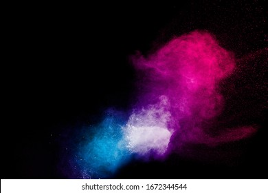 Multicolored powder explosion on black background.Color dust splash cloud on dark background.Launched colorful particles.