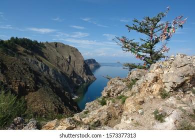 Multicolored prayer ribbons on a siberian larch-tree (Larix sibirica or Russian larch) on Cape Khoboy, Lake Baikal (Olkhon Island, Siberia, Russia)