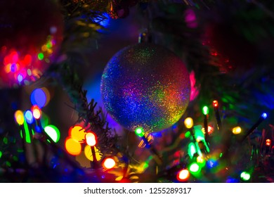 Multi-colored rainbow Christmas ball hanging on a Christmas tree. Christmas lights make the silver shiny ball colorful and rainbow. New Year, Christmas, festive background. Happy holidays!