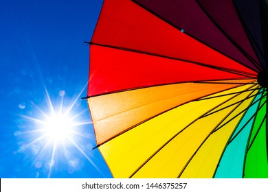Multicolored of rainbow umbrella in bottom view for protect skin from the sun, high uv on the blue summer sky with white fluffy clound. Freedom in the blue sky.