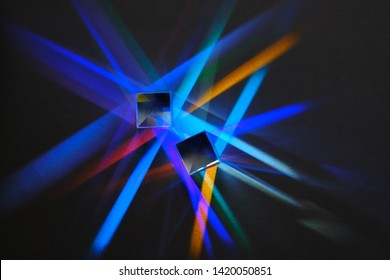 multicolored rays of light are refracted and divided into a spectrum in a glass prism on a dark background