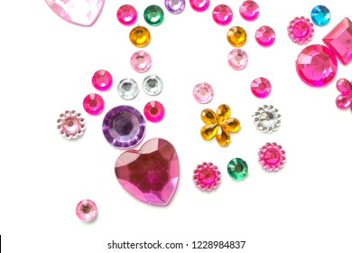 Multicolored rhinestones in the form of hearts and flowers, round rings isolated on a white background