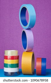 Multicolored rolls of sticky tape on lilac background.