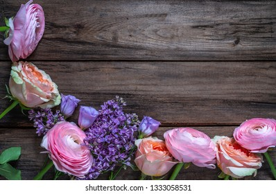 Multicolored roses and a branch of lilac on a wooden surface.Top view.Copy space.