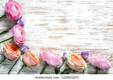 Multicolored roses on a white wooden surface.Top view.Copy space.
