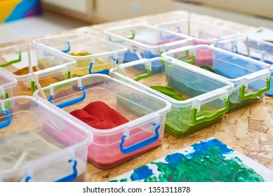Multi-colored sand for drawing in plastic containers, close-up