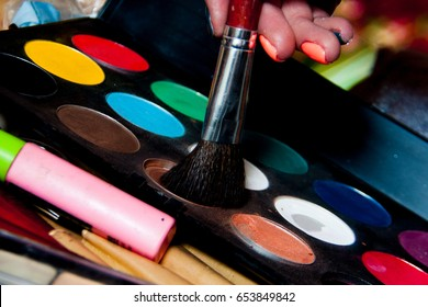 Multi-colored shadows with a brush and a female hand with painted nails
