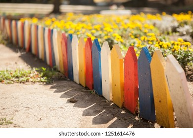 Multi-colored small fence around the flowerbed. Close-up