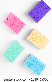 Multicolored sponges for cleaning on the white table. Blue, green, pink, yellow and purple foam rubber sponges