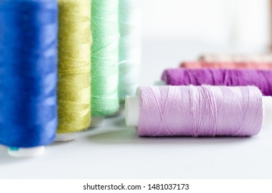 Multi-colored spools of sewing threads close-up. Craft and hobby concept
