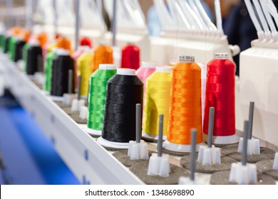 Multicolored spools of thread. Coils are installed in the feed unit of an industrial sewing machine.