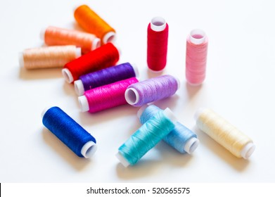 multicolored spools of thread on white background