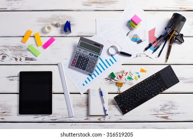 Multi-colored stationery. Office life.Workplace. Stationery and gadgets on a wooden background.