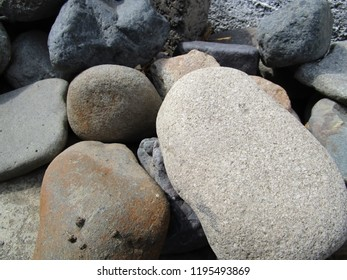 Multicolored stones of different sizes, randomly packed into a heap
