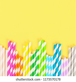 Multi-colored straw paper tubes on a bright yellow pastel background. Top view, copy space.
