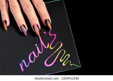 Multicolored striped nail design on long sharp shape with black lacquer.Color signature the word nails.A glamorous manicure.
