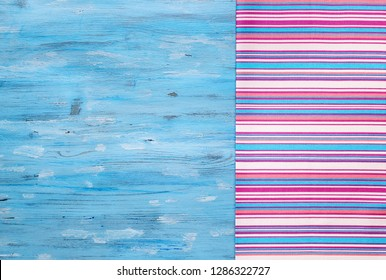 Multi-colored striped napkin from left side of turquoise painted old board, abstract food background