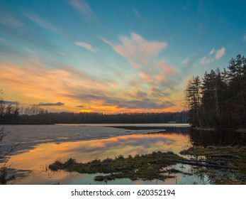 Multicolored sunset on the lake in Karelia in early spring