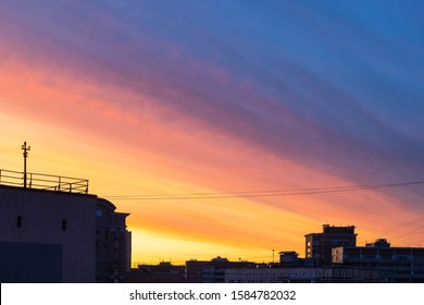 multi-colored sunset sky over urban apartment houses in autumn evening