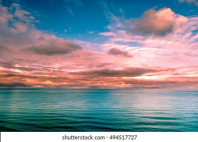 Multicolored surreal sunset view of a sea horizon. Beautiful landscape photography. Background tecture for travel and adventure.