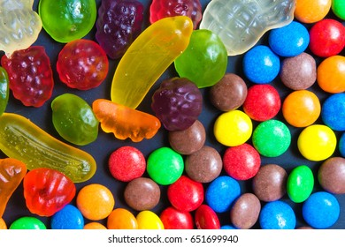 Multicolored sweets in the form of a dragee on a dark background pattern frame background