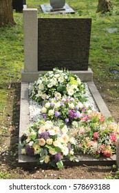 Multicolored sympathy flowers on an old grave