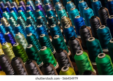 Multicolored threads on spindles in rows