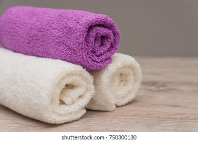 Multicolored towels on a wooden background lying next to each other