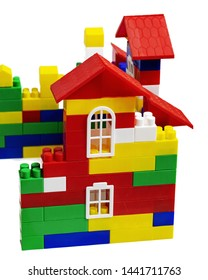 Multi-colored toy house from plastic cubes on a white background.  Is isolated