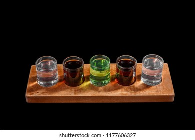 Multicolored transparent cocktails, a set of shots in one row, five servings on a wooden stand, substrate. Side view Isolated black background. Drink for the menu restaurant, bar, cafe