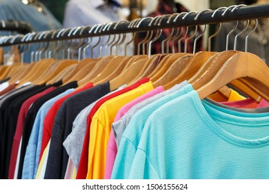 Multi-colored t-shirts with long sleeves on wooden hangers, a side view.
