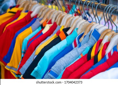 Multi-colored t-shirts on a hanger. Clothing store.