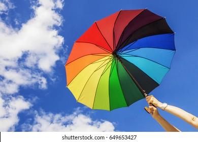 Multi-colored umbrella on the sky background