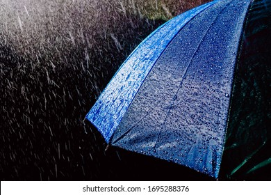 Multicolored umbrella under raindrops isolated on black as background.