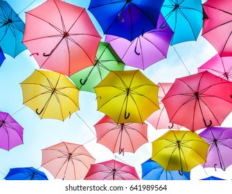 Multi-colored umbrellas background. Colorful umbrellas floating above the street. Street decoration.