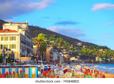 Multicolored umbrellas on the beach in Alassio, province of Savona, Sanremo region, Italy. City at sunset