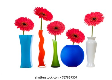 Multicolored vases and pink gerberas isolated on white background. Beautiful flower for congratulations and a gift. Still life.