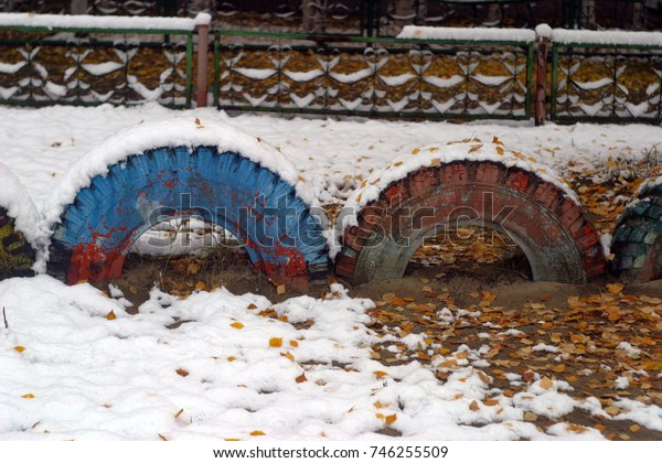 Multicolored wheels of cars dug into the ground. Playground, in the city courtyard. Snowdrift, white snow with fallen yellow leaves of trees. The first snow in the fall. Autumn, winter background