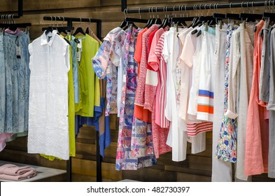 Multi-Colored Women's Clothing On Black Wooden Hangers. Blouses, Shirts, Trousers, Jackets.