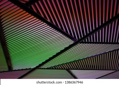 Multi-colored wood battens are formed by the light of the led lamp that comes into the wood battens in the background.