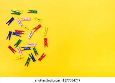 Multicolored wooden clamps lie chaotically on a yellow background. Top View. Copy space