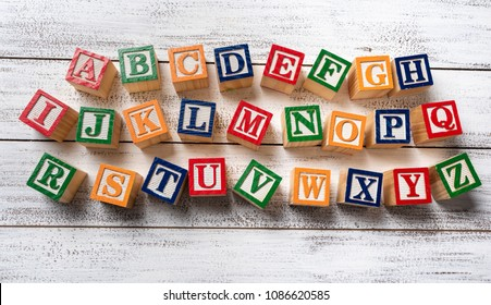 Multi-colored wooden letter blocks making the alphabet on white wood background