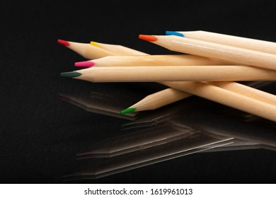 Multi-colored wooden pencils. Dark black background. Natural materials. Stationery. Office tools. Back to school. Education and art. Free space for text.