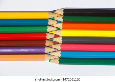 Multicolored wooden pencils interwoven on white background