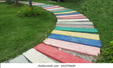 Multicolored wooden plates alternately laying in the garden path.