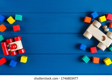 Multicolored wooden toys cubes, pyramid and cars on classic blue background. Set colorful toys for games in kindergarten, preschool kids. Close up, top view, copy space