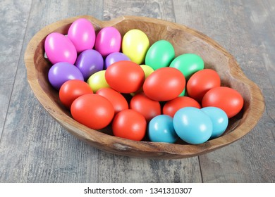 Multicoloured Easter eggs in a beautiful wooden bowl on a table