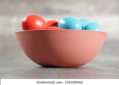 Multicoloured Easter eggs in a clay bowl on a wooden table