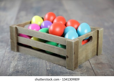 Multicoloured Easter eggs in a large wooden box on a table