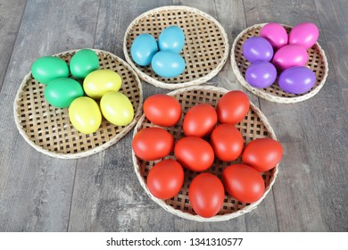 Multicoloured Easter eggs on wicker straw stands on wooden table